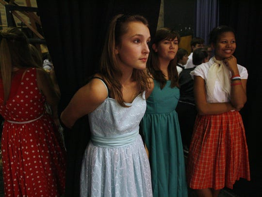 Dancers wait in the wings off stage before they rehearse