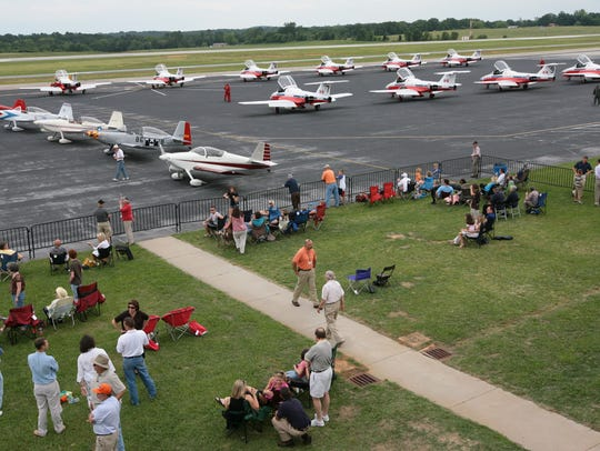 A row of Canadian Snowbirds planes are parked before