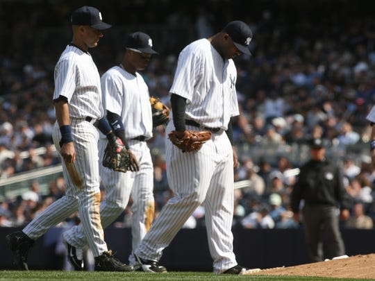 The first game at the new Yankee Stadium and Opening Day.  Yankees Derek Jeter, Robinson Cano and CC Sabathia head back to the mound just before manager Joe Girardi came out and pulled Sabathia in the 6th inning.