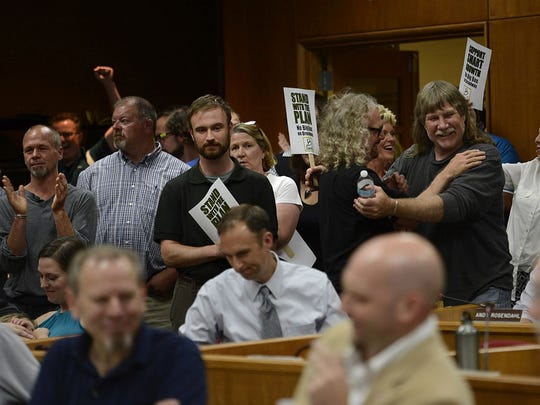 People react after the Green Bay City Council voted early Wednesday against Walmart's proposal for big-box store.