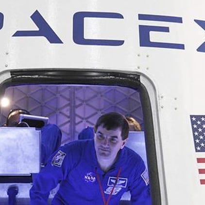 NASA astronaut Rex Walheim checks out the Dragon spacecraft at SpaceX headquarters in Hawthorne, Calif in 2012.