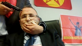 An alleged militant from the Turkish Marxist-Leninist left wing organization, the DHKP-C, holds a gun to the head of prosecutor Mehmet Selim Kiraz.