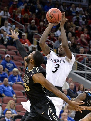 Cincinnati's Shaq Thomas (3) shoots over Purdue's Raphael Davis during the first half of an NCAA tournament second round college basketball game Thursday, March 19, 2015, in Louisville, Ky. (AP Photo/Timothy D. Easley)
