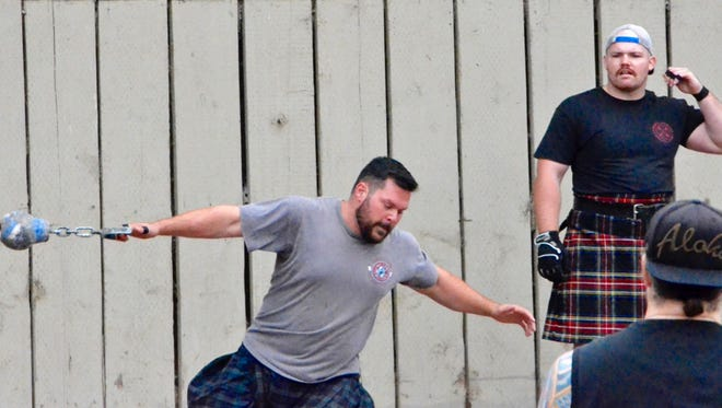 Tossing a weight far in front of him, an athlete competes at the Scottish Games