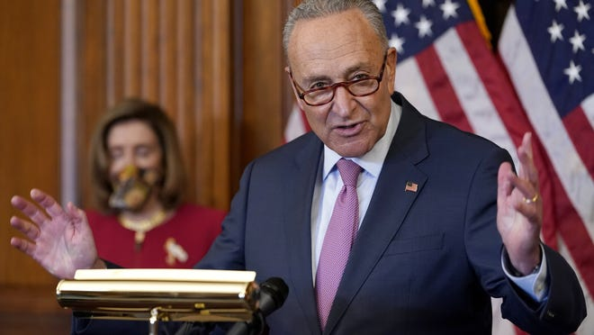 Senate Minority Leader Sen. Chuck Schumer of N.Y., right, speaks next to House Speaker Nancy Pelosi of Calif., during a news conference about COVID-19, Thursday in Washington.