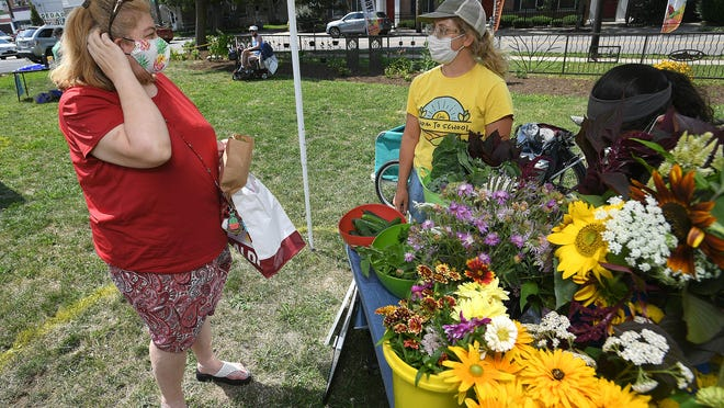 Erin Gallenstein, at left, of Erie, talks with Stephanie Ciner, at right, owner of Wild Field Farm in Erie, on Monday. Ciner was one of seven vendors at the Little Italy Farmers Market, 331 W. 18th St. in Erie, which will be open from 3-6 p.m. every Monday through September.