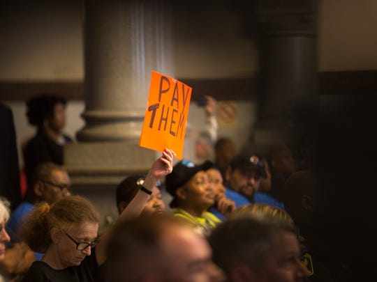 "A person holds a sign that says ""Pay Them."""