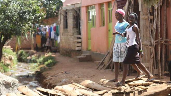 Natalia Peni, 19, on right, walks through her neighborhood in Kampala, Uganda, with her cousin Jane Aniiri, 18.