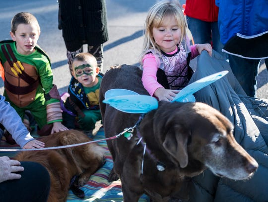 Emma Kelton, 4, (right) stops with other trick-or-treaters to pet a dog named Kona at the Henderson United Democratic Women's Club booth during the Community Trunk or Treat Extravaganza last year.
