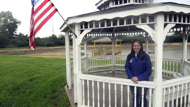Ashland County Parks director Stephanie Featheringill poses inside the gazebo at Tom Kruse Wildlife Conservation Park on County Road 1754 at Ohio 60 on Thursday, In the background the finished handicap accessible fishing pier can be seen.