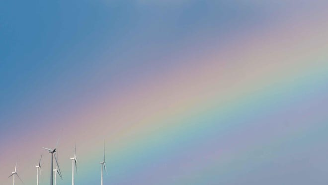A wind farm in western Kansas stands tall against a rainbow backdrop.