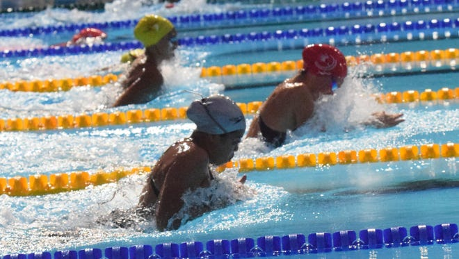 The top three finishers in the women's 100-meter breaststroke pop out of the water at the same time, with Guam's Pilar Shimizu (near, silver cap) chasing eventual gold medalist Adeline Williams from New Caledonia (center, red cap) and bronze medalist Savana Tkatchenko (rear, yellow cap). Shimizu won the silver at the Pacific Games in Port Moresby, Papua New Guinea.