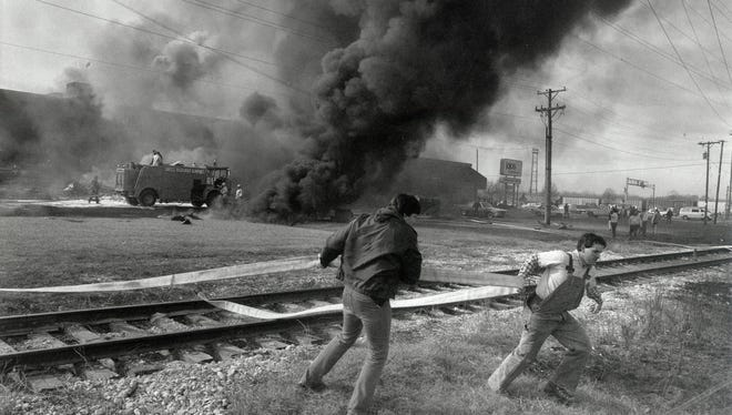 Emergency personnel haul fire hoses at the site of the C-130B military cargo plane crash at the Drury Inn and JoJo's Restaurant site Feb. 6, 1992.