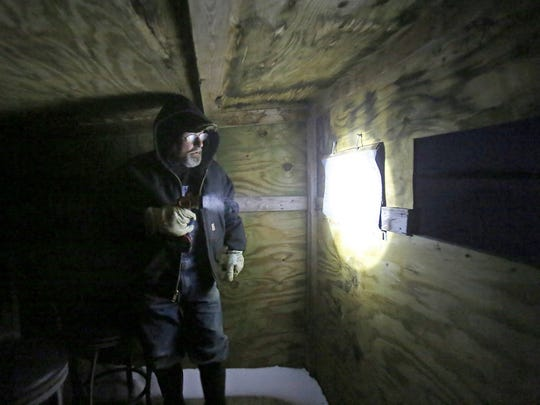 Guiding by flashlight, Carl Flaig directs early morning visitors into a blind for up-close views of prairie chickens on his farm near Rudolph, Wis. Thursday, April 5, 2018. Flaig, an organic dairy and beef farmer, has four blinds on his property that he rents out for birders.