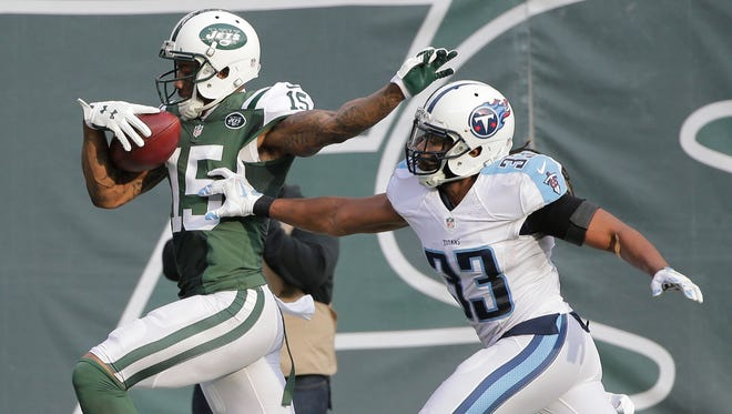 New York Jets wide receiver Brandon Marshall (15) runs past Tennessee Titans' Michael Griffin (33) for a touchdown in the first half.
