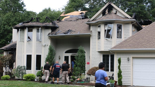 A family friend stands in front of the Bassaly home at 197 Church Pond Drive in Tiverton as fire officials investigate the cause of a fatal blaze that broke out late Monday afternoon.