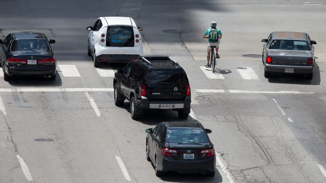 A bicyclist sits at the intersection of Pennsylvania and Ohio Streets, Indianapolis, Wednesday, July 9, 2014.