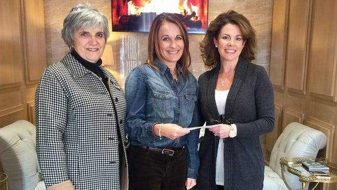 Jill Czanstkowski accepts a donation from Beverly Morton (left) and Lori Gregory (right) the Downtown Merchants organization to support the Mountain Home Public Schools' Bridges program.