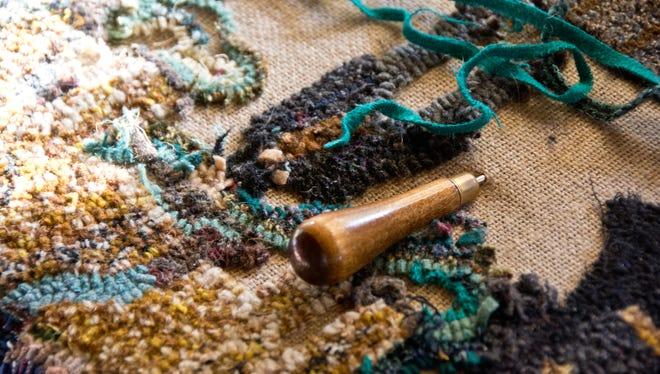 A rug hook project is shown in progress.