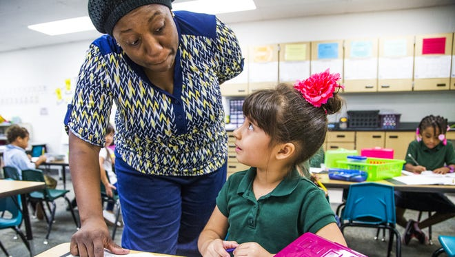 Sheely Farms Elementary School kindergarten teacher Tamara Jackson helps Sophia Chavez in class in October.