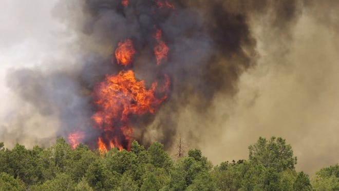 Flames leap more than 100 feet in the air as the Rodeo-Chediski fire burns up a ridge line in 2002.