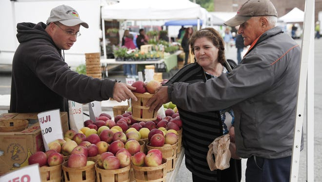 Robert Johnson, one of the owners of Johnson Produce of Williamson, left, sells apples to customers Merie and Wadih Sossine at the new Lakeside Farmers Market in Charlotte on the corner of Lake Avenue and Stutson Street. The market will be at this location every Monday beginning at 4 p.m.