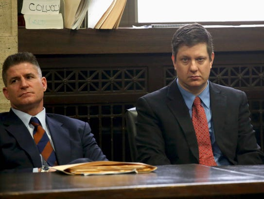 Chicago Police officer Jason Van Dyke, right, charged with murder in the 2014 videotaped shooting death of black teenager Laquan McDonald, sits in court with his attorney, Dan Herbert, on March 23, 2016, for a status hearing in his case.