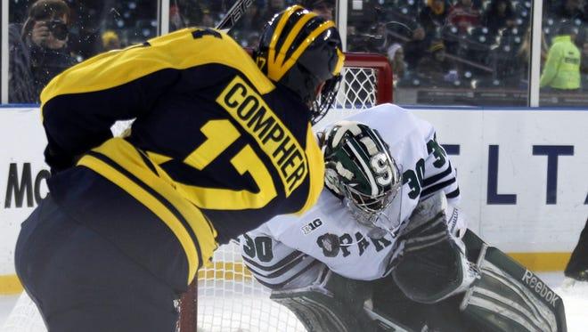Michigan State goalie Jake Hildebrand blocks shot by Michigan forward JT Compher on Dec. 28,  2013.