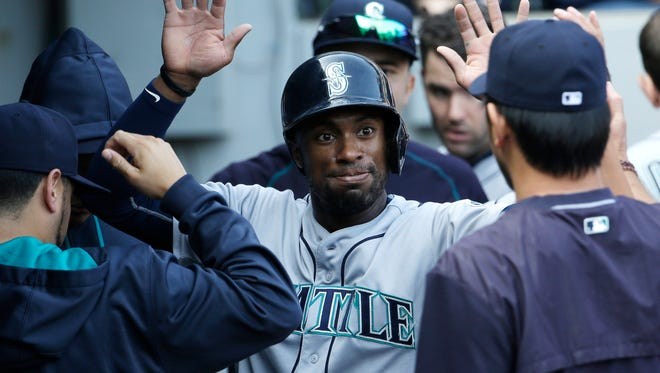 Seattle Mariners' Austin Jackson celebrates with teammates after scoring on a single by Kyle Seager on Aug. 30, 2015.