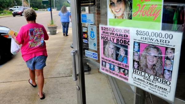 Several different posters calling attention to the missing Holly Bobo, adorn the door of the Cornerstone Family Pharmacy in Decatur County.