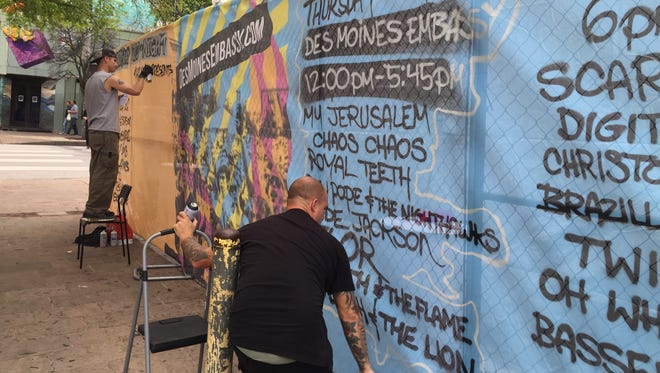Graffiti artists illustrate the outside banners of the Des Moines Embassy at SXSW.