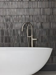 Modern bathtub and faucet with slate grey tiled wall