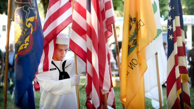 A member of the color guard places a flag at the annual Flag Day ceremony Tuesday, June 14, 2016, at Fisher Veterans Park in Lebanon.  The Lebanon Elks Lodge, Community of Lebanon Association and Lebanon Valley Sertoma Club sponsored the event.
