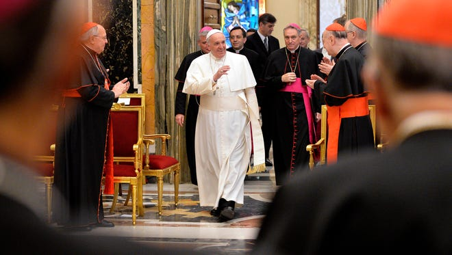 Pope Francis waves to Cardinals and Bishops of the Vatican Curia during a meeting on the occasion of the exchange of Christmas greetings in the Clementine hall at Vatican, Monday, Dec. 22, 2014. (AP Photo/Andreas Solaro, Pool)
