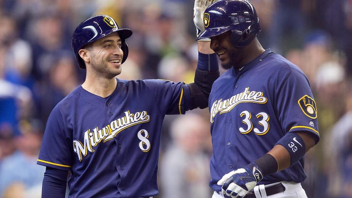 Ryan Braun congratulates Chris Carter at home plate after Carter's home run in the third inning. Carter and Braun combined for six of Milwaukee's 18 hits Sunday, with Carter hitting two homers and a double and Braun contributing three singles.