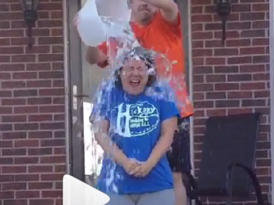 Jolene Benedict of Burlington is dumped with a bucket full of ice by her husband, Ron, in the ALS Ice Bucket Challenge. Provided