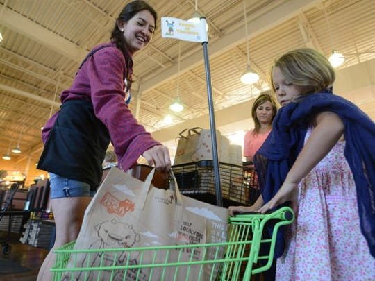 Cashier, Ona Fisher, left, puts a bag of groceries into Elliana Beno's kids cart at Whole Foods market.