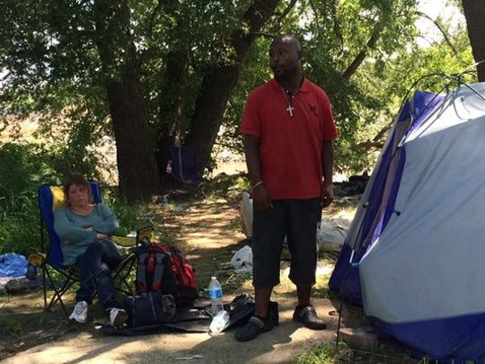 Laurie Garland and Eric Rodgers spend a final day Monday at their campsite along the Raccoon River, near the Martin Luther King Jr. Parkway bridge. The city has begun dismantling such campsites. On Monday, fewer than a dozen people remained in them.