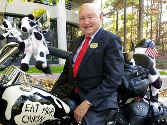 In this Nov. 8, 2001, file photo, S. Truett Cathy, founder of Chick-fil-A, poses on a Harley Davidson motorcycle which is painted to look like a cow, in front of the company's headquarters in south Atlanta.