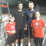 Singles champion Theo Fournerie, second from left, and runner-up Ben McLachlan are flanked by ball kids Cole Anderton, left, and Sachi Marshall.
