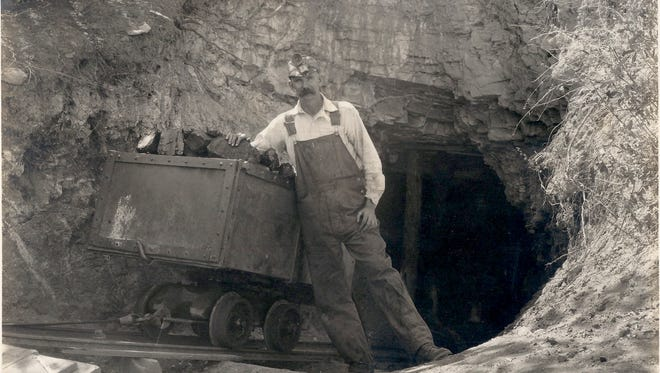 An unidentified miner wearing headgear poses as he leans on a cart at the entrance to a White Oaks mine. A rolling mine cart on railway was used for moving ore or materials procured in the process of traditional mining.