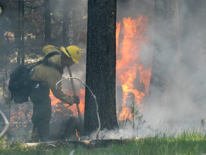 A firefighter works around a hot spot that flared up