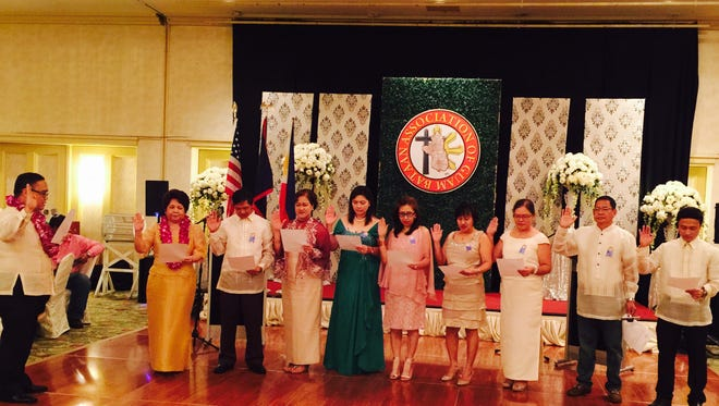 Consul Mark Hamoy administers the oath of office to the officers of the Bataan Association during their induction ceremony.
