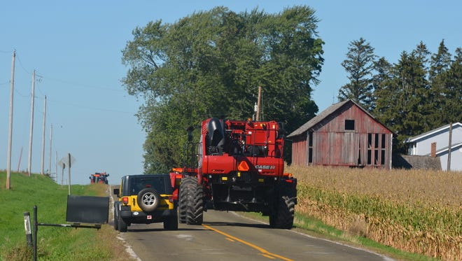 An SUV illegally passes an combine in a no passing zone.