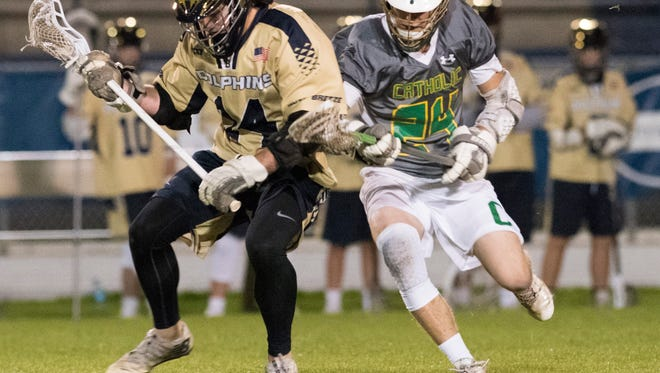 Gulf Breeze High School's Chris Durst, (No. 24) and Catholic High School's William Butler, (No. 24) battle for possession at midfield during Thursday night's lacrosse match at Dolphin Stadium in Gulf Breeze.