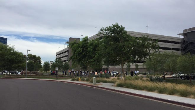People stand outside the Tempe office after the all-clear.