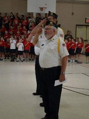 Photo is of the Jackson American Legion Post #504 representatives and students from St. Aloysius School saluting the flag.