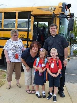 Photo is of Fr. Bambrick, Pastor, Vice Principal Nancy Hegedus, Math teacher Jen Nase and two kindergarten students.