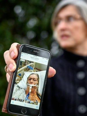 Jeannine Thelen shows a picture from April of herself connected to a breathing machine while in the hospital battling COVID-19 on Wednesday, Nov. 18, 2020, at her home in Lansing. Thelen was Sparrow Hospital's first COVID-19 patient and spent 55 days in the hospital and a month on a ventilator fighting the virus.