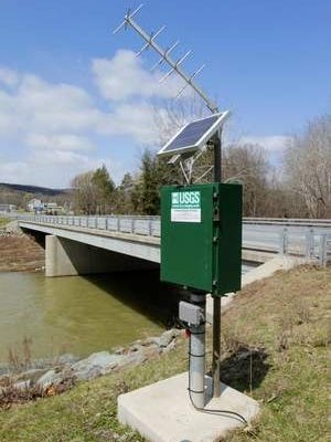 This U.S. Geological Survey stream gauging station at Owego Creek stands just south of the state Route 96 bridge over Owego Creek, visible in the rear.